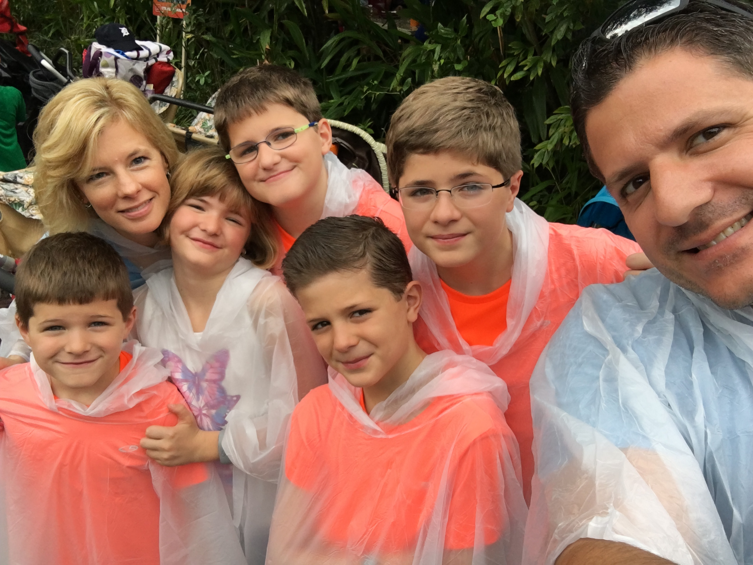 This is me and my family right before we went on a water ride. Thats why were wearing those weird bag things called ponchos.